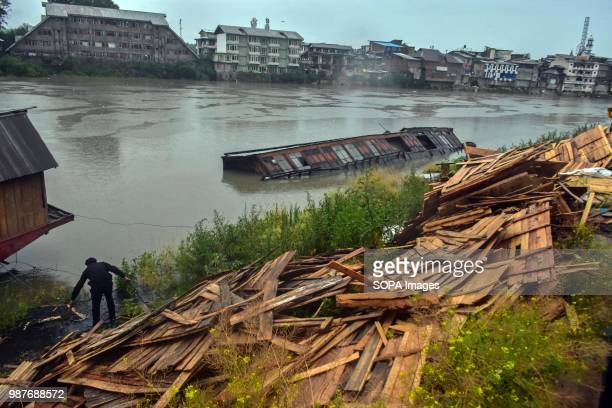 A man collects the wooden sheets from a damaged houseboat A flood alert has been sounded in Kashmir in the wake of continuous rains since Wednesday...