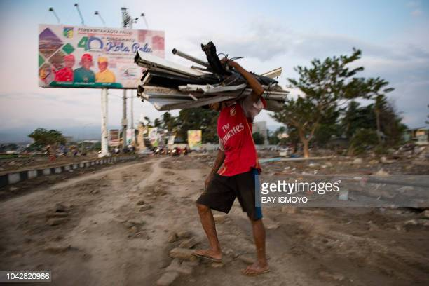 TOPSHOT A man collects valuable material from a beach that was hit by a tsunami in Palu in Central Sulawesi on September 29 after a strong earthquake...