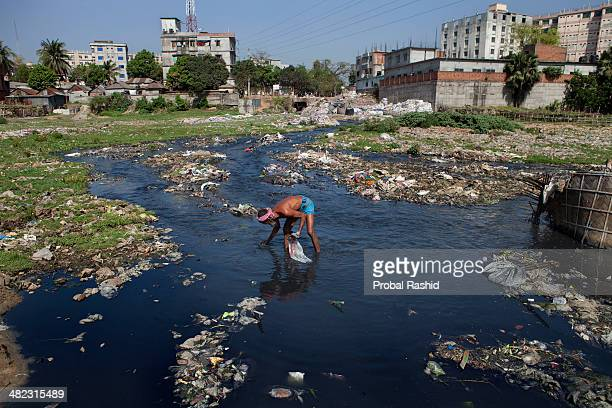 A man collects waste plastic for recycling from the untreated chemical waste of factories The factories are discharging untreated chemicals into the...