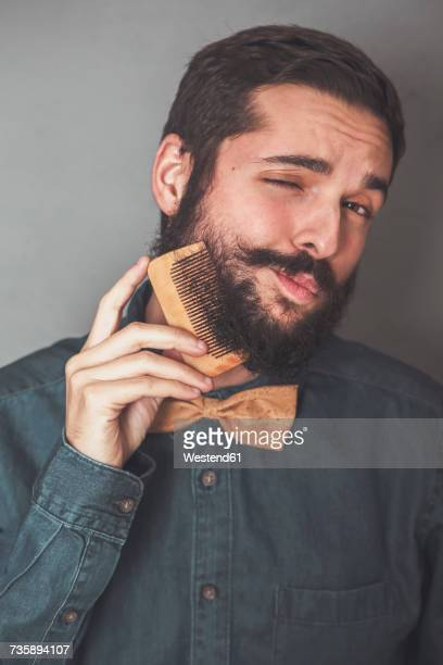 man combing his beard with a wooden comb, wearing denim shirt and cork bow tie - barba peluria del viso foto e immagini stock