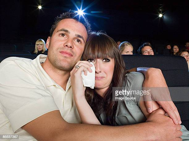 A man comforting a woman watching a sad movie