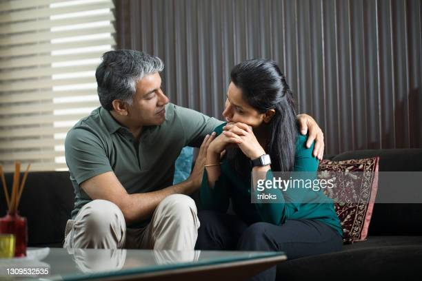 man comforting his wife at home - wife stock pictures, royalty-free photos & images