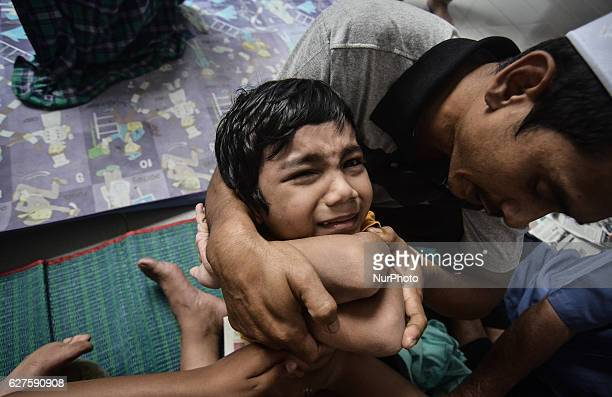 A man comforts a boy as he under goes circumcision during ceremony at a mosque in Bukit Mertajam outside George Town Malaysia on December 4 2016...