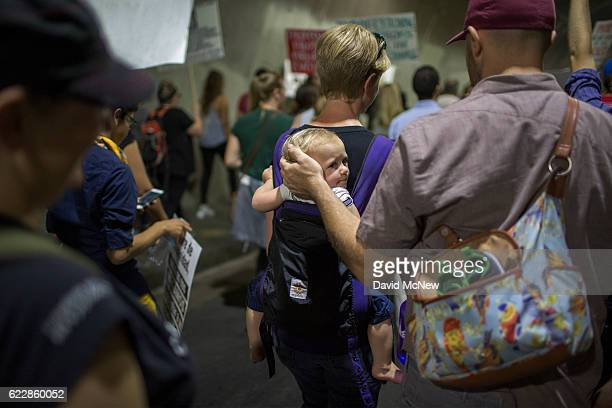 A man comforts a child as the echoes of chants become loud while marching through a tunnel in reaction to the upset election of Republican Donald...