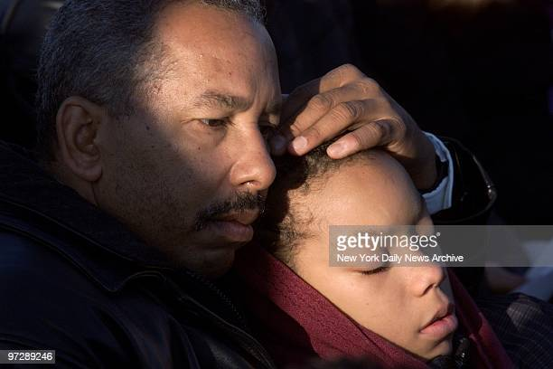 Man comforts a child during a prayer service for victims of the crash of American Airlines Flight 587 at Jacob Riis Park in the Rockaways Queens The...