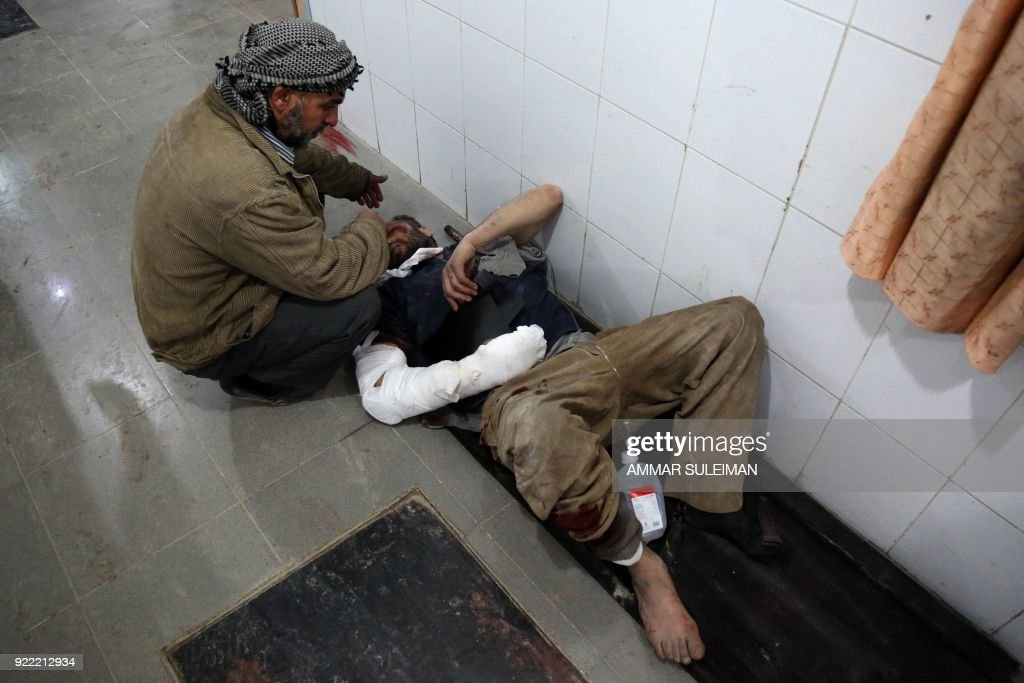 A man comforts a wounded Syrian man waiting for treatment at a make-shift hospital in Kafr Batna following Syrian government bombardments on the besieged Eastern Ghouta region on the outskirts of the capital Damascus on February 21, 2018. Syrian jets carried out more deadly raids on Eastern Ghouta as Western powers and aid agencies voiced alarm over the mounting death toll and spiralling humanitarian catastrophe. PHOTO / Ammar SULEIMAN
