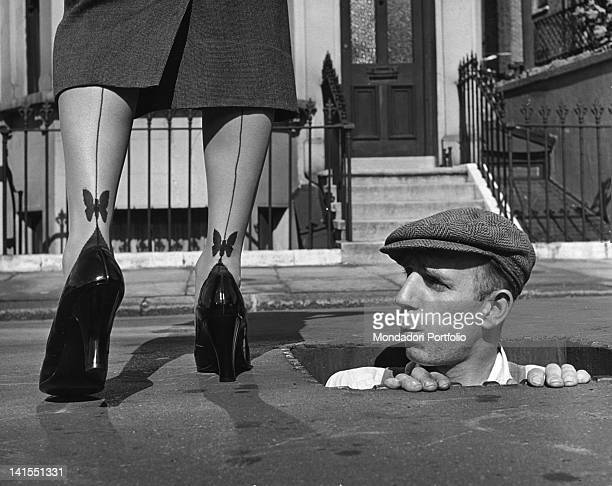 Man coming out of a manhole looking at the ankles of a woman and whistling The woman is wearing seamed nylon stockings with two embroidered...