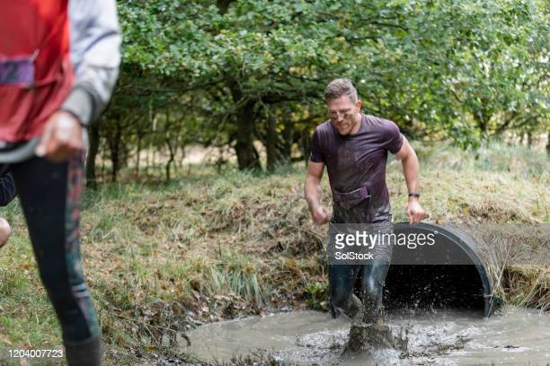 man coming out of water tunnel on outside obstacle course - caucasian appearance stock pictures, royalty-free photos & images