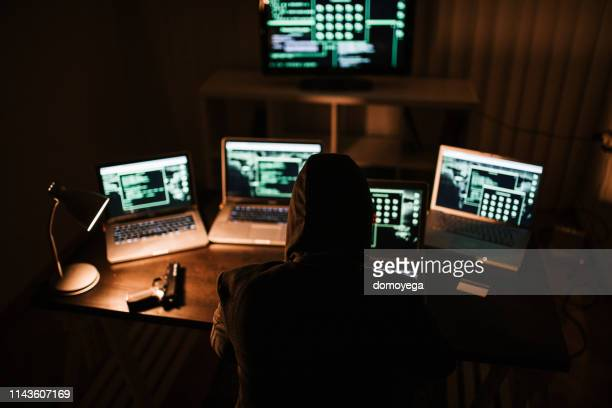 man committing crime and stealing online information - pirata informatico foto e immagini stock
