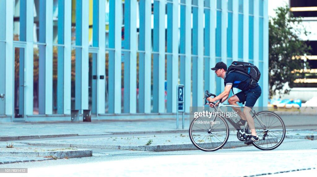 男女事務所ビルを過ぎて自転車に乗って通勤して : ストックフォト
