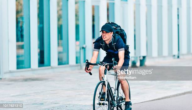 Man commutes to work on racing bicycle while wearing backpack