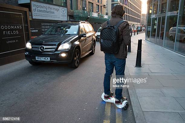 Man commuting on his hoverboard passes other traffic going in the opposite direction London England UK A selfbalancing twowheeled board or...