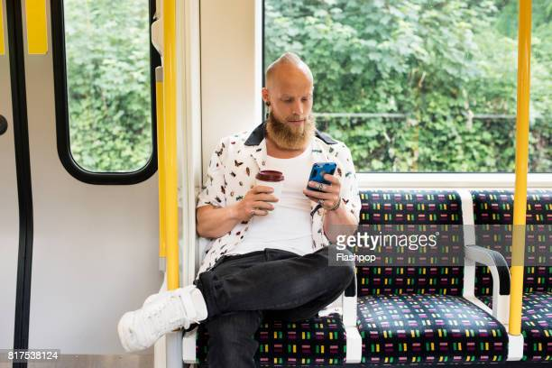 man commuting on train using phone - train interior stock photos and pictures
