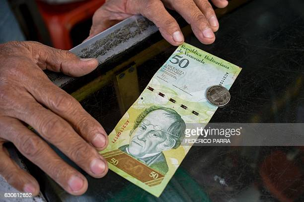 A man compares a new 50Bolivarcoin with a Bolivarnote of the same denomination at a kiosk in Caracas on December 28 2016 Venezuela took delivery on...