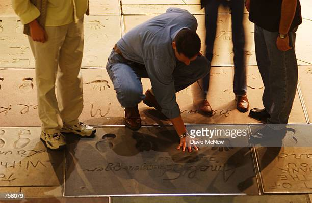 A man compares his hand to the hand and foot prints that stars have left in concrete for some 80 years at the original Grauman's Chinese Theatre...
