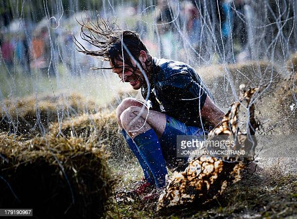 Man competes during the 10000 Volt obstacle as he competes during the Tough Viking race on September 1, 2013 in Stockholm. The course of the Tough...