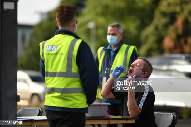 Man completes a self-administered COVID-19 test at a walk-in testing centre in Bolton, northern England on September 9 as local lockdown restrictions...