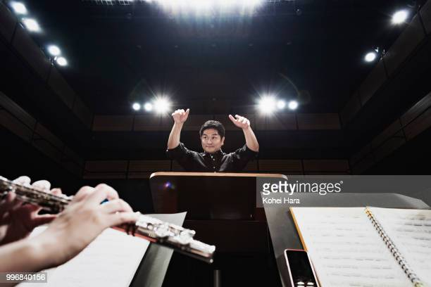 Man conducting an orchestra at concert hall