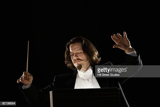 Man conducting behind music stand