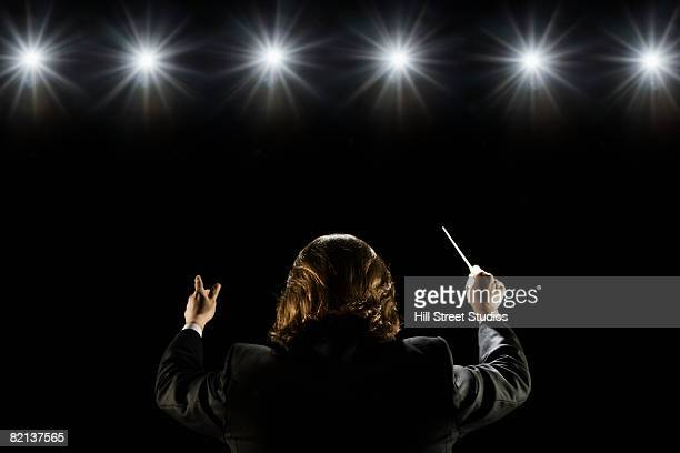 man conducting under lights - maestro stock photos and pictures