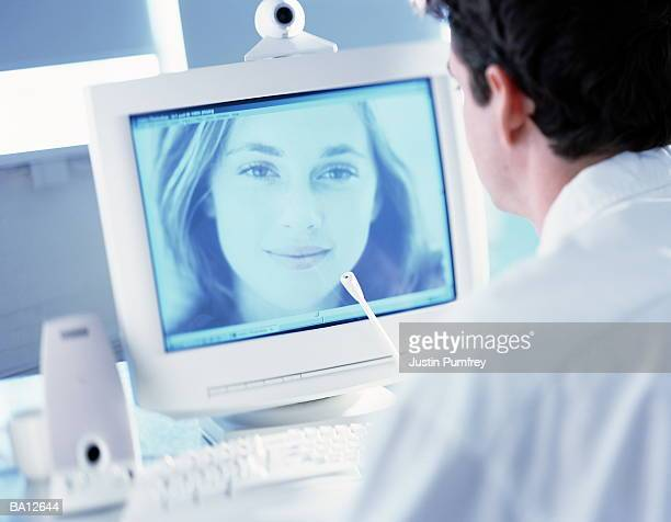Man conducting video conference on computer, view over shoulder