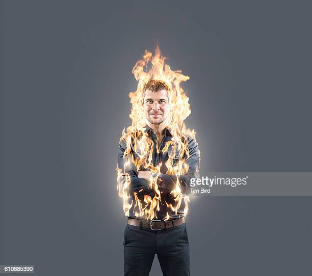 man confidently poses with arms folded whilst on fire - burning stock pictures, royalty-free photos & images