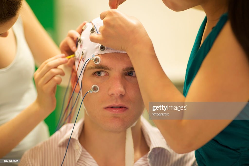 man connected with cables to computer - EEG for resarch : Stock Photo