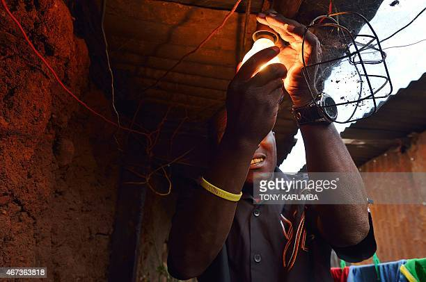 A man connects a lightbulb to power supplied through an illegal connection in a slum in the Kenyan capital Nairobi March 23 2015 Illegal electricity...