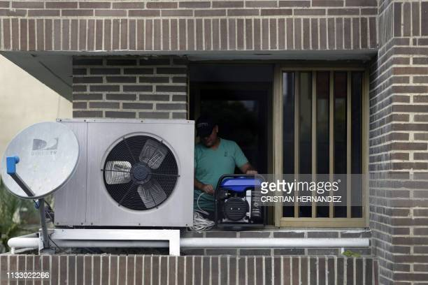 A man connects a portable power generator at his apartment in Caracas Venezuela on March 26 2019 Venezuela decreed a 24hour holiday Tuesday to cope...