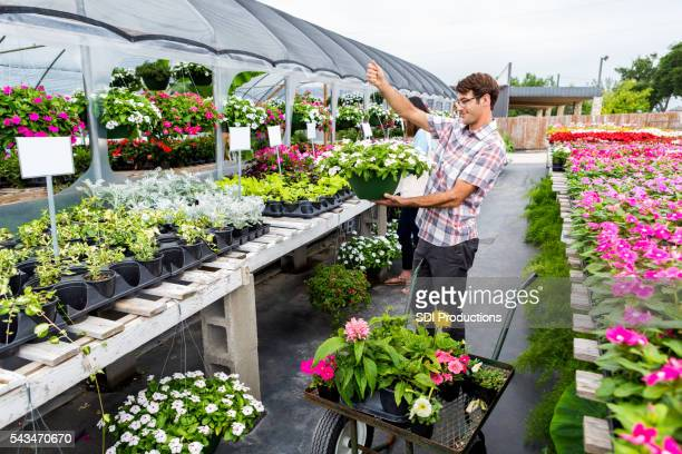 Man considers buying hanging basket at nursery
