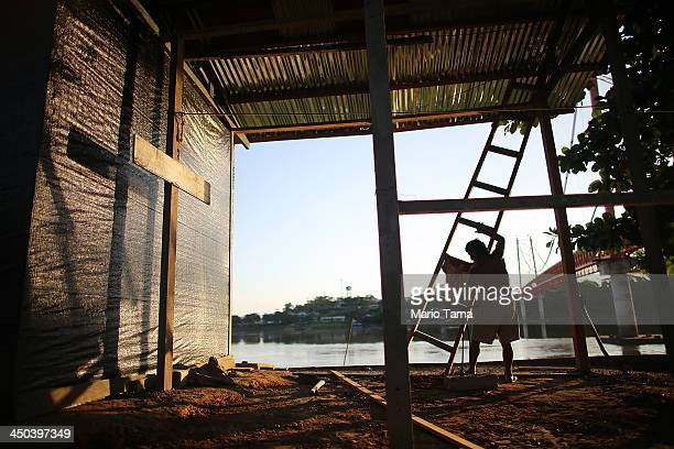 A man constructs a home along a deforested section of riverbank in the capital of the Madre de Dios region a boomtown located at the confluence of...