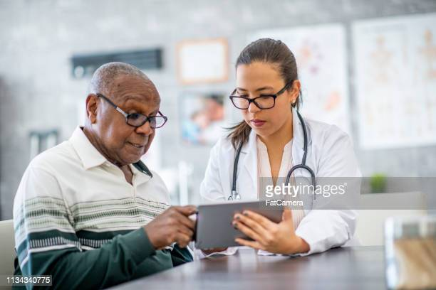 man consults with his doctor - dementia stock pictures, royalty-free photos & images
