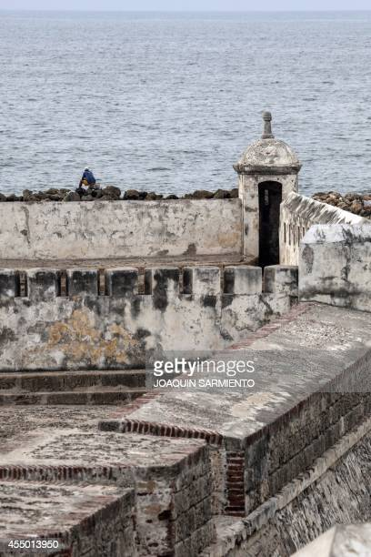 A man contemplates the sea outside the historic fortress walls of Cartagena Colombia on September 8 2014 The city of Cartagena celebrated on Monday...