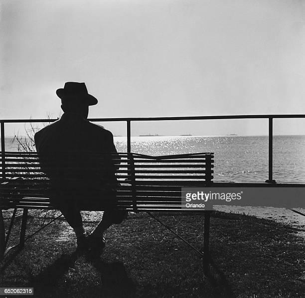 A man contemplates the setting sun over the horizon circa 1955
