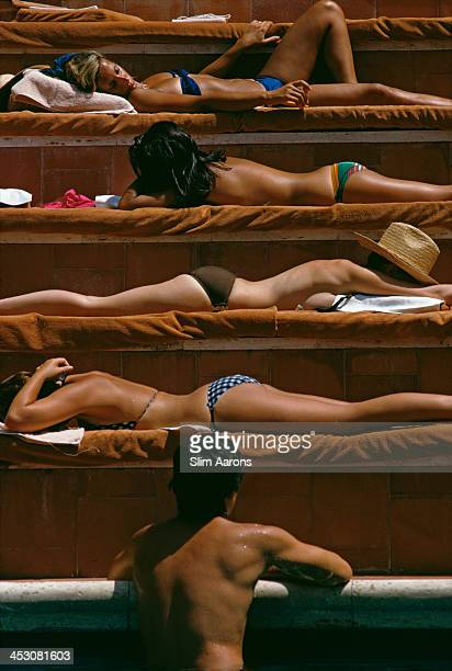 A man contemplates the sunbathers by a swimming pool at the Hotel Punta Tragara on the island of Capri Italy August 1974
