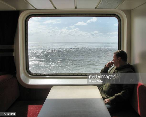 Man contemplating life, sea travel, ferry crossing, Holland looking in the distance,