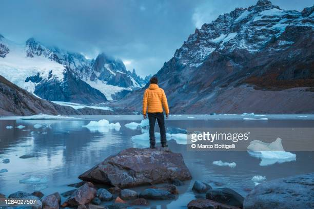 man contemplating melting ice on glacier lagoon - iceberg ice formation stock pictures, royalty-free photos & images