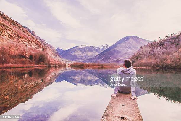 man contemplating the beautiful water reflection on the lake from the dock with the beautiful mountain landscape of the catalan pyrenees in a road trip. - reflection lake stock photos and pictures