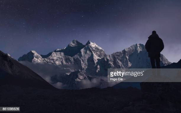 a man contemplating the mountains under the moonlight - khumbu stock pictures, royalty-free photos & images