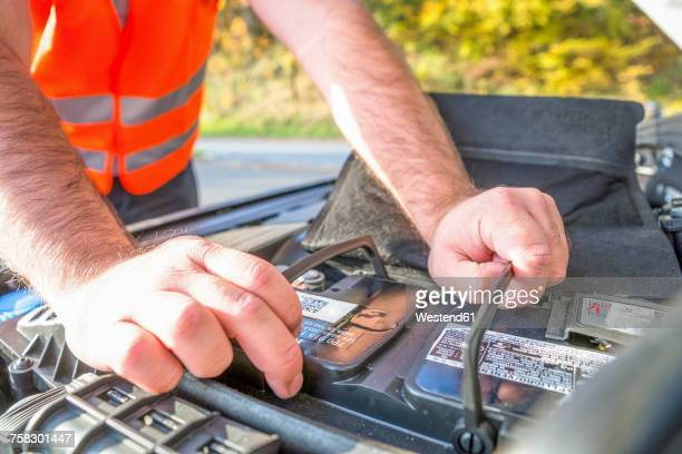 Man controlling car battery, close-up