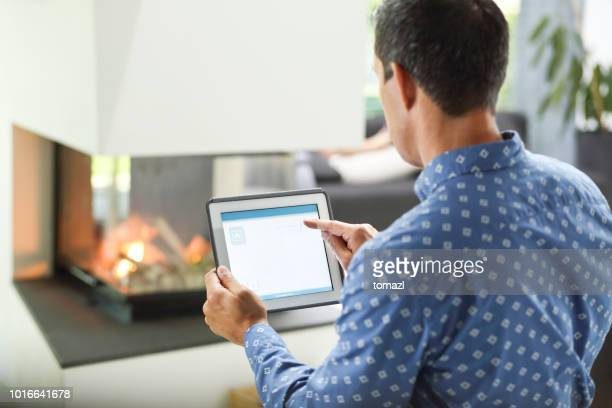 Man controlling fireplace on his tablet - smart home concept