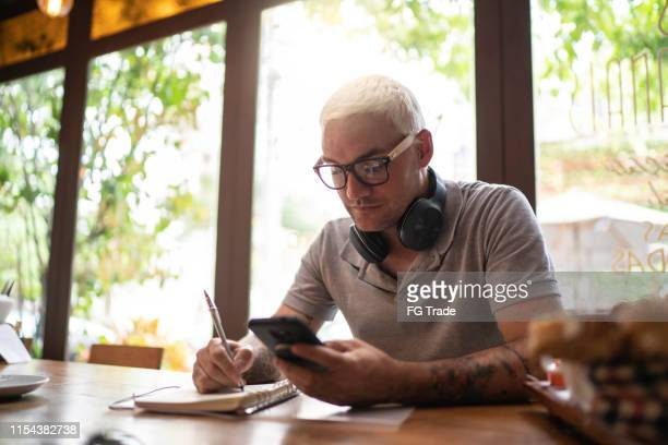 man controlling his finance using a digital investment platform and taking notes - financial technology stock pictures, royalty-free photos & images
