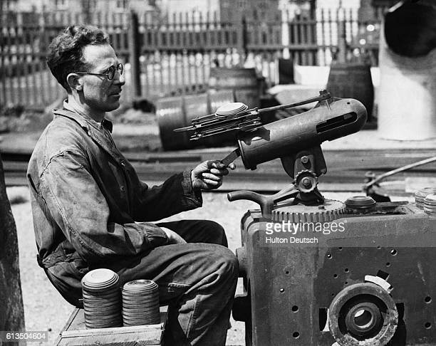 A man controls a machine that releases clay pigeons for target practice The clay pigeons have been painted red white and blue for a shoot to...