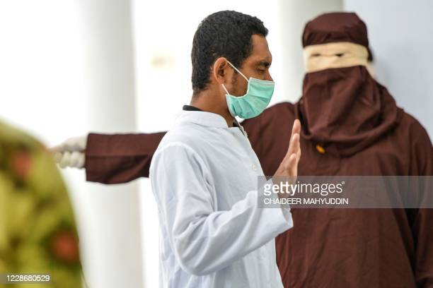Man, convicted of engaging in sexual activity with a minor, is flogged by a member of the Sharia police in a public building in Banda Aceh on...