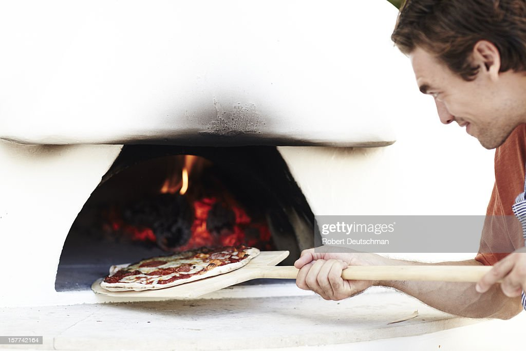 A man cooking a woodfire pizza. : Bildbanksbilder