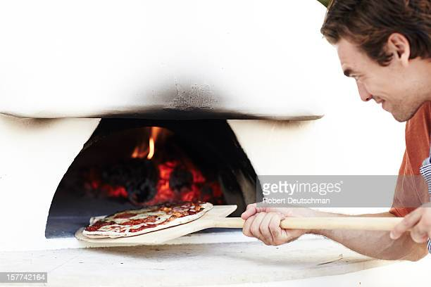 A man cooking a woodfire pizza.