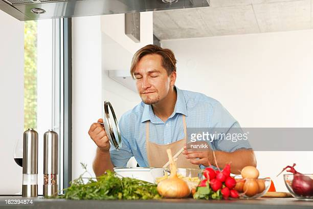 Man cooking and smelling his boling meal