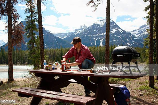 Man cooking at campground picnic table