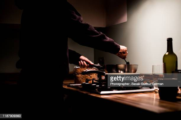 a man cooking at night in the kitchen - domestic kitchen stock pictures, royalty-free photos & images