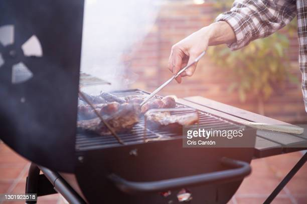 man cooking beef steaks and sausages on grill - cris cantón photography fotografías e imágenes de stock